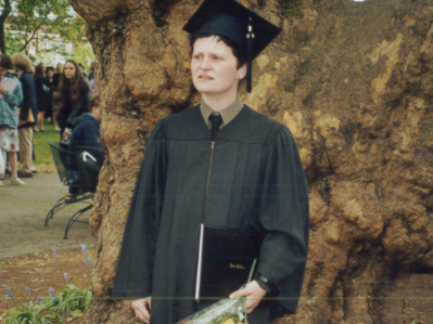image of me looking confused while wearing academic graduation regalia and holding my diploma and a bunch of flowers