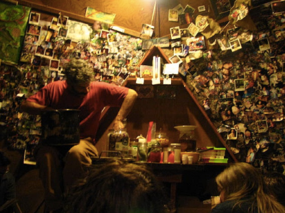 imgae of person making sauerkraut in front of a wall covered in polaroid pictures
