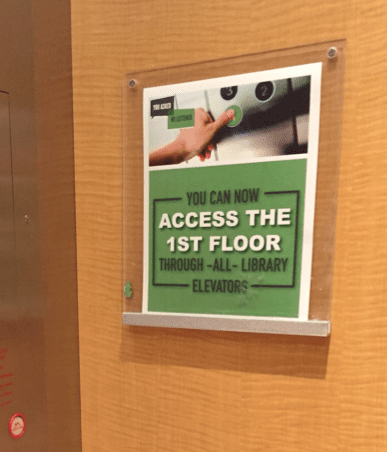 sign reading 'you can now access the 1st floor through all library elevators""